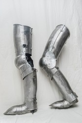 Steel set of armor for protecting legs from the 14th - 15th centuries. Part of knightly equipment, white background.