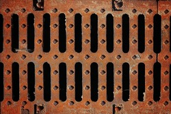 Steel sewer grate.Rough screws. Dark holes. Rusty grunge manhole. Metallic industrial background. Metal texture