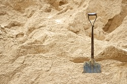 Steel shovel be used for scoop sand to construct the building background, front view.