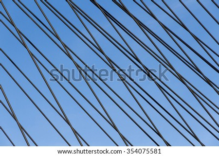 Steel Straps on a Cable-Stayed Bridge - Detail of metal braces or wires of a cable stayed bridge fan design #354075581