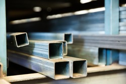Steel structural channels, tubes and pipes of different sections and sizes on shelves. Metalworking industry concept