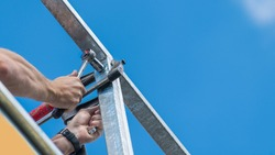 Steel structure assembly. Screwing by ratchet wrench in craftsman hands. Worker tightening a bolt in clamped metal construction. Close-up of mounting of terrace or balcony rail on blue sky background.