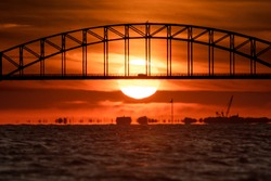 Steel tied arch bridge over water with a sunset behind it. Telephoto large sun - Fire Island Inlet Bridge, Long Island.