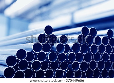 Steel tubes against industrial blurred background