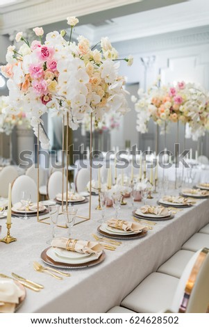 Steel vases with orchids stand on dinner table Сток-фото ©
