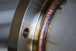 Steel weld joined pipe to plate by arc welding process . rainbow color.with copy space