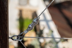 Steel wire attached to an eye hook with a steel cable clamp in a plant climbing aid made from stainless steel in the garden