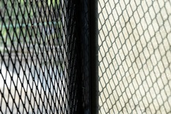 Steel wire of railings or baluster with black columb for guard or protect around the building,a shadow on raw concrete floor like net texture to strip of shadow on cement.Light spilled through it.