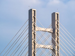 Steel wires bridge structure. Close up with metal cable structure of a modern suspension bridge against blue sky.