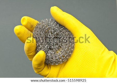 steel wool for cleaning the kitchen in his hand