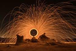 Steel wool photography at the desert rock structure at night time with fire splash all over. Slow Shutter speed photography with steel wool