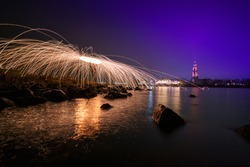 Steel wool photography involves setting light to steel wool and then spinning it in the air to create sparks that light up the dark night sky, creating patterns of light during a long exposure.