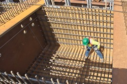 Steel workers tying rebar in a concrete form for casting a concrete post tension integral pier cap, the steel girders are encased in the concrete pier and not attached to the top of the pier cap