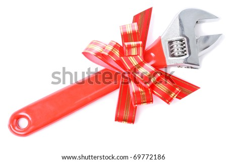 Steel wrench with red plastic handle and red goldish striped bow as a gift for handyman isolated on white background