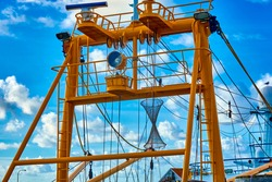Steel yellow painted superstructures and masts of a trawler for catching fish, mussels and crabs