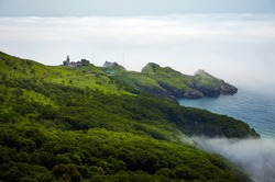 Steep cliff above the sea in the fog. Gamow Lighthouse on the Gamow Peninsula. Dangerous Bay in the Sea of Japan. Far East.