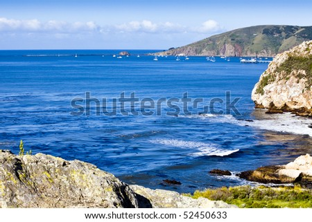 Steep Cliffs frame the bay at Avila Beach, California,  and the fishing harbor at Port San Luis, in the distance