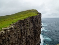 Steep cliffs of Faroe Islands. Green grass at the top, Ocean below the cliffs.