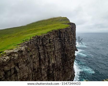 Steep cliffs of Faroe Islands. Green grass at the top, Ocean below the cliffs.  Photo stock ©