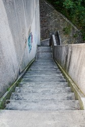 Steep concrete stairs leading down to a stone wall. High concrete wall with graffiti. View from above.