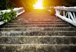 Steep concrete stairs with beautiful sunlight at above. Old grunge staircase with white handrail among green trees at Lad Koh view point. Up stair in the morning. Concept about effort for success.