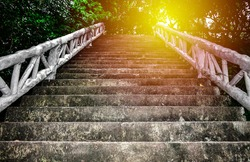 Steep concrete stairs with beautiful sunlight at above. Old grunge staircase with white handrail among green trees at Lad Koh view point. Attraction in Samui Island, Thailand. Up stair in the morning.