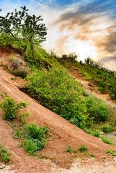 Steep descent along a path along a clay slope against a vibrant sky.