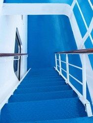 Steep gangway on a cruise ship, white and blue color. Ship ladder