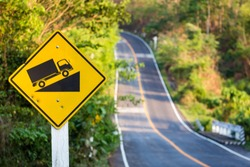 Steep grade traffic sign on the roadside, uphill asphalt road in countryside