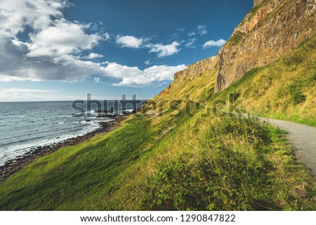Steep green slope with tourist path. Northern Ireland. The grass covered hill next to the ocean. Overwhelming Irish shoreline scene. Blue cloudy sky background. Perfect touristic site. #1290847822