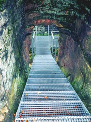 Steep metal stairs of construction in rocks to elimination of weathering and scaling of soft sandstone. Staircase  leading to the top in the castle ruin hiking trail