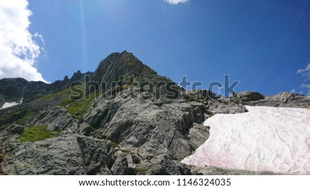Steep rock scree on slopes of a mountain overlooking Aletsch Glacier on a sunny Summer day - Switzerland