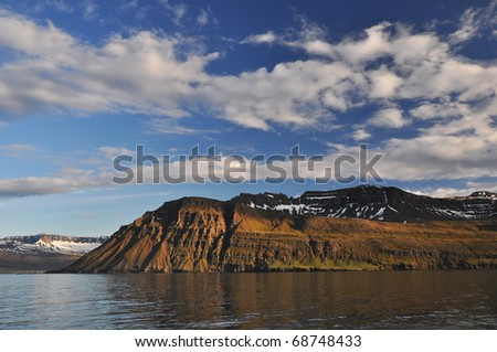 Steep rocky fjord and beautiful sky, East fjords Iceland
