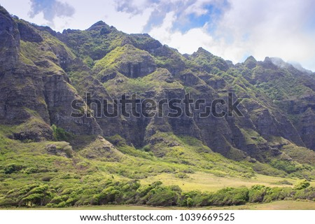 Steep, rugged, volcanic mountains rise up into the clouds above the lush green valley of a tropical island in Hawaii.