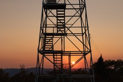 Steep stairs leading up a mountain fire tower as the sun sets on the horizon. Overlook Mountain, New York