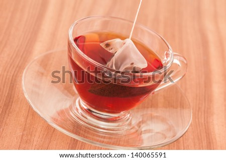 Steeping pyramid mesh tea bag in a glass cup on a wooden table