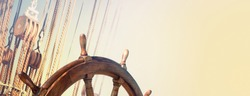 Steering wheel and marine ropes on the old ship for your concept of marine voyage under sails. Nautical equipment on ancient sailing vessel with a wooden wheel of captain.