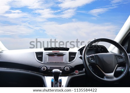 Steering wheel of a modern car with Car dashboard and beautiful blue sky background.Technology,Transport,Vacation,Holiday,Travel and Automobile Concept. #1135584422