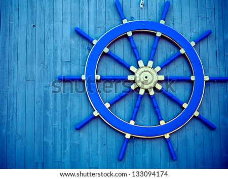 Steering wheel of the ship on a wooden wall of restaurant in marina