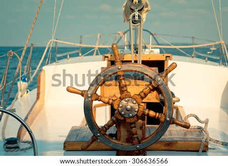 Steering wheel on the old sailboat. Sea voyage of the sailing vessel. Travel at sail boat with a wooden helm in front. Ship wheel on the old yacht - nautical equipment closeup. #306636566