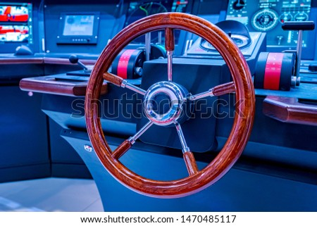 Steering wheel on the remote control ship. Steering wheel and ship throttles on the captains bridge. Modern ship control panel. #1470485117