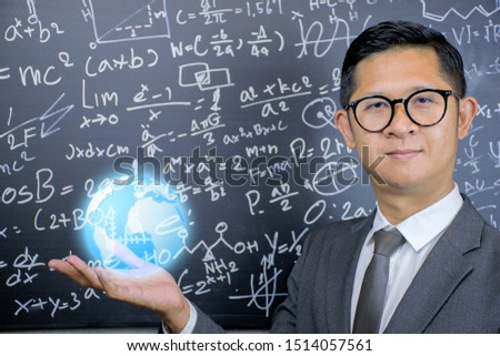 STEM concept.Mathematics teachers wear glasses, wear suits, look dignified, trustworthy.He opened his hand and had a globe on it.The background is a blackboard with mathematical formulas.