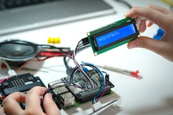 STEM Education, Closeup hands of young student successfully code and connect blue character LCD display screen to Raspberry pi and Micro:bit in lab,  Experiment, Electronics, Sci-Tech, School project.