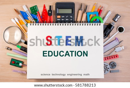 STEM education text on notebook over school supplies or office supplies on school table. Background with school or office material with copy space for text. #581788213