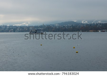 Stemboat on the Lake of Zurich with the background of foggy mountains with snowy tops. Wintertime. Scenery. Blue and grey colours. Sightseeing. Travelling.   #796183024