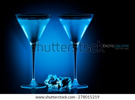 Stemmed cocktail glasses with blue liquor and ice cubes on the table, closeup isolated on black. Template design with sample text