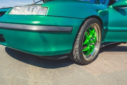 Stence culture.Sports green car. Tuning. Rubber on stylish wheels. Underestimated cars