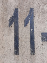 stencil number in spray paint, spray painted of character 11 on old cement floor for background, black stencil number on concrete