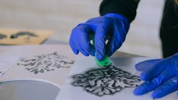 Stencil painting: close up shot of woman hands painting wooden circle. Paint, handmade and crafting work concept