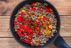 Step-by-step cooking of Chili con carne, step 5 - adding chopped pepper to the meat, top view, horizontal